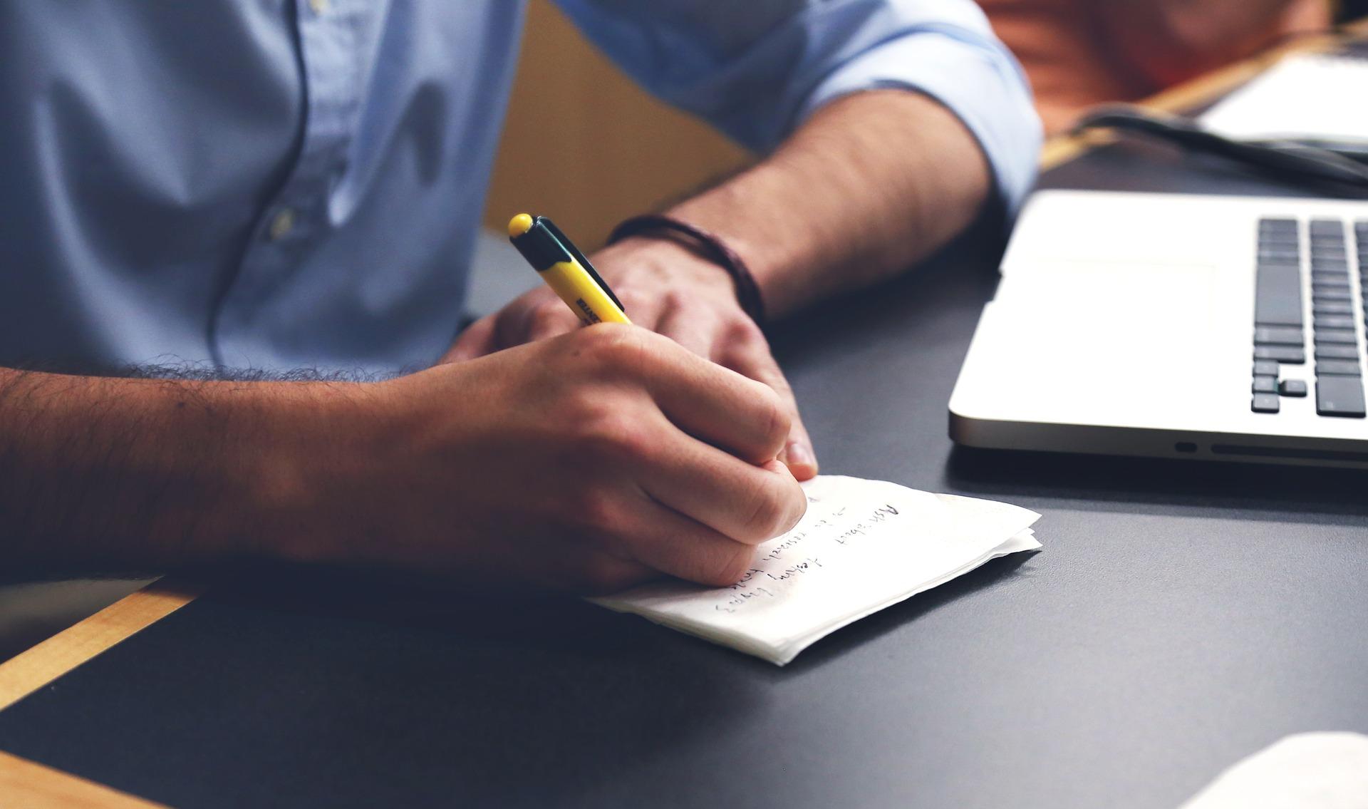 紙にペンで書いているところ
